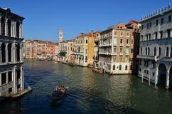 Opinião da ponte os turistas em um barco no canal em Veneza, Itália Imagem de Stock