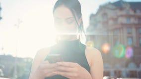 Opinião da rotação de uma morena bonita usando seu telefone, sorrindo felizmente à tela, texting ativamente para trás em um brilh vídeos de arquivo