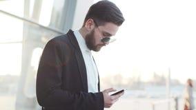 Opinião da rotação um homem à moda nos óculos de sol que estão pelas portas do aeroporto e que usam seu telefone video estoque