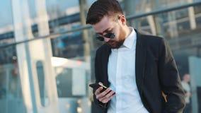 Opinião da rotação um homem farpado novo nos óculos de sol que estão pelo terminal de aeroporto e que usam seu telefone Negócios video estoque