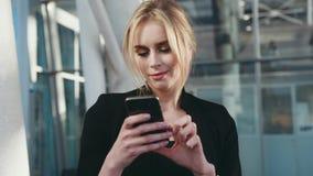 Opinião da rotação uma mulher loura nova bonita em uma blusa elegante preta usando seu smartphone no terminal de aeroporto vídeos de arquivo