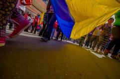 Opinião da rua de debaixo da bandeira gigante do ecuadorian durante o anti março e protestos do governo em Quito Imagens de Stock
