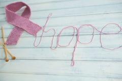 Opinião de ângulo alto da fita cor-de-rosa da conscientização do câncer da mama pelo texto e pelas agulhas de crochê da esperança Fotos de Stock