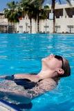 Opinião de ângulo alto da menina bonita nos óculos de sol e do roupa de banho que descansa na piscina fotos de stock royalty free