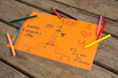 Opinião de ângulo alto do cartão com os pastéis coloridos na tabela Imagens de Stock Royalty Free