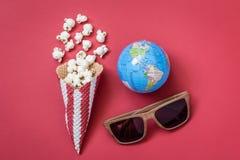 A opinião de ângulo alto do cone com os monóculos da pipoca e do cinema com globo modela no conceito minimalistic do fundo vermel Fotos de Stock Royalty Free