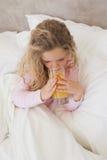 Opinião de ângulo alto do suco de laranja bebendo da menina na cama Foto de Stock
