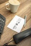 Opinião de ângulo alto do telefone, do café, da pena e do bloco de notas Foto de Stock