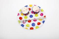 Opinião de ângulo alto dos queques na placa colorido contra o fundo branco Imagens de Stock