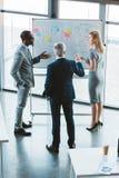 opinião de ângulo alto a equipe multi-étnico profissional do negócio que discute cartas e gráficos fotografia de stock