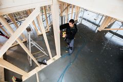 Opinião de ângulo alto o carpinteiro Drilling Wooden Plank Foto de Stock Royalty Free