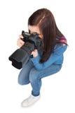 Opinião de ângulo alto o fotógrafo novo ocasional que toma a imagem fotografia de stock