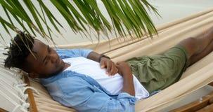 Opinião de ângulo alto o homem afro-americano que dorme em uma rede na praia 4k filme