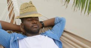 Opinião de ângulo alto o homem afro-americano que dorme em uma rede na praia 4k vídeos de arquivo