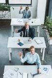 opinião de ângulo alto os executivos alegres nos auriculares que sorriem na câmera fotos de stock royalty free