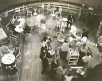 Opinião de ângulo alto os povos na sala de estar de cocktail a bordo do navio Fotografia de Stock Royalty Free