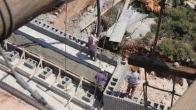 Opinião de ângulo alto os trabalhadores da construção que derramam o concreto no canteiro de obras vídeos de arquivo