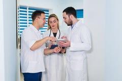 Opinião de ângulo alto três doutores nos revestimentos brancos que têm a conversação no salão do hospital imagem de stock