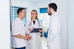 Opinião de ângulo alto três doutores nos revestimentos brancos que têm a conversação no salão do hospital fotografia de stock