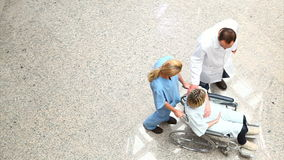Opinião de ângulo alto uma enfermeira que roda um paciente em uma cadeira de rodas filme