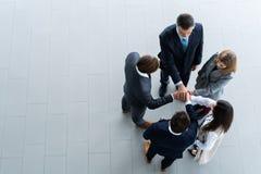 Opinião de ângulo alto uma equipe dos colegas de trabalho unidos que estão com suas mãos junto em uma aproximação no escritório m fotografia de stock royalty free