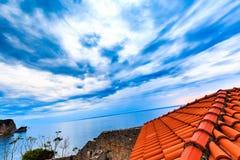 Opinião de ângulo larga do telhado das telhas vermelhas a ajardinar Céu dramático com as nuvens de tempestade sobre o mar Imagem de Stock Royalty Free