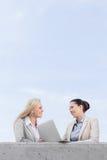 Opinião de baixo ângulo as mulheres de negócios novas felizes com portátil que discutem ao estar no terraço contra o céu Imagem de Stock Royalty Free