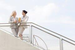 Opinião de baixo ângulo as mulheres de negócios novas que falam ao estar cercando contra o céu Fotos de Stock Royalty Free