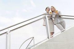 Opinião de baixo ângulo as mulheres de negócios novas que guardam copos de café descartáveis ao estar cercando contra o céu Fotos de Stock