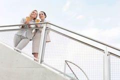 Opinião de baixo ângulo as mulheres de negócios novas que guardam copos de café descartáveis ao estar cercando contra o céu Foto de Stock Royalty Free