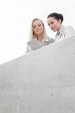 Opinião de baixo ângulo as mulheres de negócios novas que usam a tabuleta digital junto ao estar no terraço contra o céu Fotografia de Stock