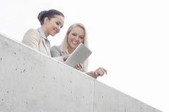 Opinião de baixo ângulo as mulheres de negócios novas que usam a tabuleta digital no terraço do escritório contra o céu Imagens de Stock Royalty Free