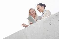 Opinião de baixo ângulo as mulheres de negócios novas que usam a tabuleta digital no terraço do escritório contra o céu Fotos de Stock Royalty Free