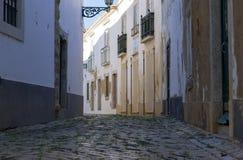 Opinião de baixo ângulo da rua cobbled em Faro, o Algarve, Portugal imagem de stock royalty free