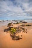 Opinião de baixo ângulo das rochas na praia Fotos de Stock Royalty Free