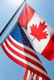 Opinião de baixo ângulo de bandeiras canadenses e americanas, Foto de Stock Royalty Free
