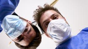 Opinião de baixo ângulo dois cirurgiões com máscaras sobre a cara vídeos de arquivo