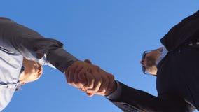 Opinião de baixo ângulo dois homens de negócios bem sucedidos que encontram e que agitam as mãos no fundo claro do céu azul Segur vídeos de arquivo