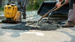 Opinião de baixo ângulo dois trabalhadores que arranjam a mistura fresca do asfalto com ancinhos e pá fotos de stock royalty free