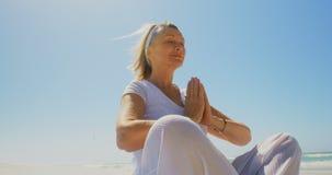 Opinião de baixo ângulo a mulher caucasiano superior ativa que executa a ioga na praia 4k video estoque