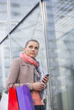 Opinião de baixo ângulo a mulher que escuta a música ao comprar Foto de Stock