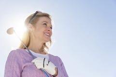 Opinião de baixo ângulo a mulher que mantém o clube de golfe contra o céu Imagem de Stock Royalty Free