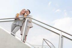 Opinião de baixo ângulo mulheres de negócios novas com os copos de café descartáveis que estão cercando contra o céu Imagens de Stock Royalty Free