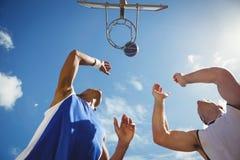 Opinião de baixo ângulo os amigos que jogam o basquetebol imagens de stock