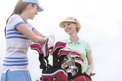 Opinião de baixo ângulo os jogadores de golfe fêmeas felizes que falam contra o céu claro Foto de Stock Royalty Free