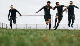 Opinião de baixo ângulo os jogadores de futebol que jogam no campo que corre para a bola Grupo de homens que correm para a posses imagem de stock