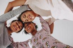 Opinião de baixo ângulo três meninas que estão junto imagem de stock royalty free