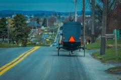 Opinião de Bavck do carrinho de Amish que viaja acima de uma estrada no Condado de Lancaster rural imagens de stock