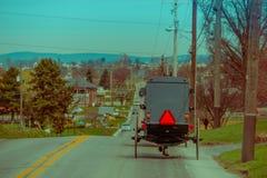 Opinião de Bavck do carrinho de Amish que viaja acima de uma estrada no Condado de Lancaster rural imagem de stock royalty free