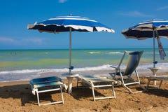 Opinião de costa de mar do adriático Litoral de Itália, guarda-chuvas do verão no Sandy Beach com as nuvens no horizonte Fotos de Stock